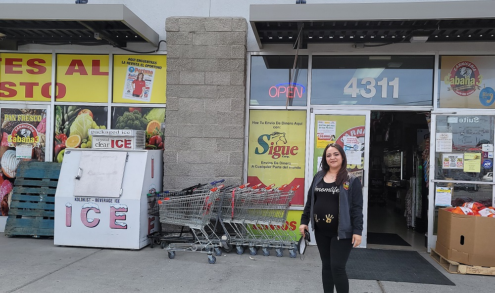 Viviana in front of her grocery store